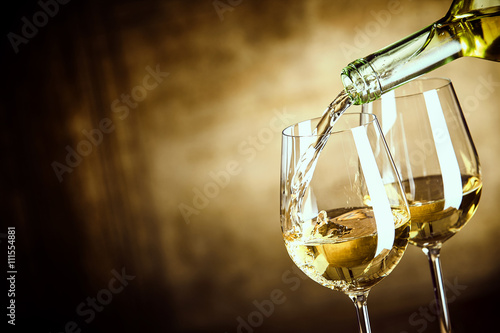 Foto auf Gartenposter Wein Pouring two glasses of white wine from a bottle