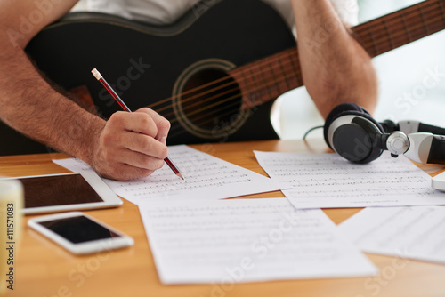 Photo Close-up image of composer examining sheets with notes