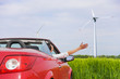 Woman in a red cabriolet in a field.