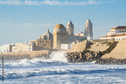 View of the Ancient Cadiz Cathedral. The waves on the winter Atlantic Ocean. Spain
