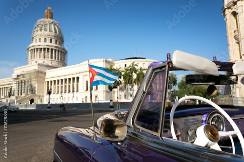 Foto op Plexiglas Havana Cuban flag on a classic car with the Capitolio on the background in Havana, Cuba