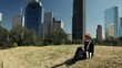 A woman sitting in a small downtown park or green space with metropolitan Houston looming in the background composes a letter while she sits and enjoys the sunshine of a mild winter day.