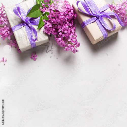 Border from wrapped gift boxes with presents and lilac flowers