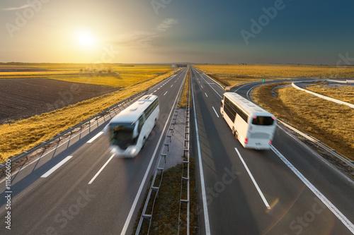 Zdjęcie XXL Szybkie autobusy na autostradzie w idyllicznym zachodzie słońca