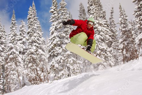 Jumping snowboarder on snowboard in mountains in ski resort Tablou Canvas