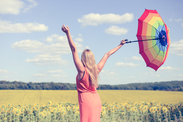 Back view of beautiful young lady holding multicolored umbrella in sunflower field and blue sky outdoors.