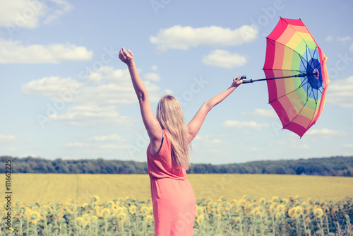Obraz Back view of beautiful young lady holding multicolored umbrella in sunflower field and blue sky outdoors. - fototapety do salonu