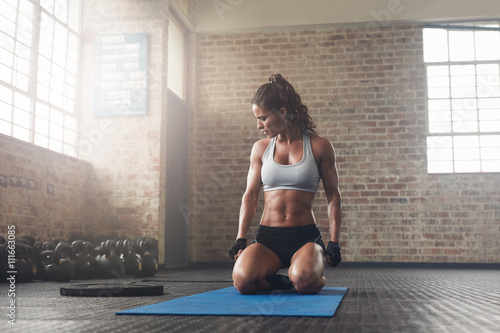 Fotografie, Obraz  Fitness young woman sitting on yoga mat at gym