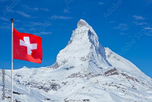 Fotografie, Obraz  Famous Matterhorn with flag of switzerland
