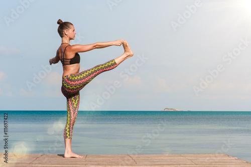 Leinwand Poster  Frau macht Yoga am Morgen am Meer. Lens Flare Effekt