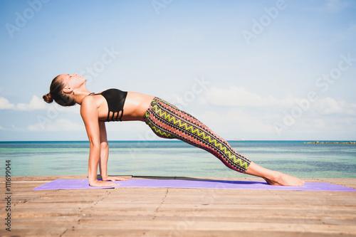 Leinwand Poster  Frau macht Yoga am Morgen am Meer.