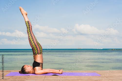 Foto  Frau macht Yoga am Morgen am Meer.
