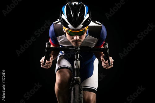 Fotografie, Obraz  Handsome young man cycling indoor. Isolated on black.