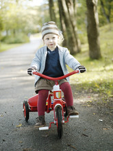 Girl Riding Tricycle On Road