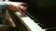 Young man plays on a piano, fast music, changing focus with camera movement