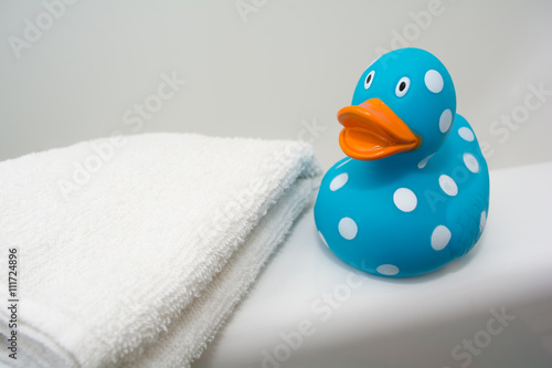 Fotografie, Obraz  Cute Rubber Duck beside a White Towel in a Bathroom
