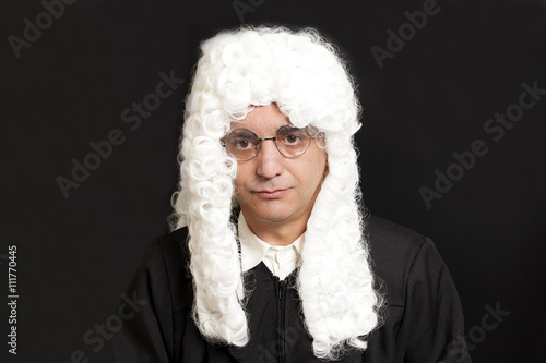 Foto  Portrait Of Male Judge in a wig on black background