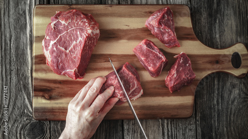 Obraz na plátne  Cutting angus beef on the wooden table top view