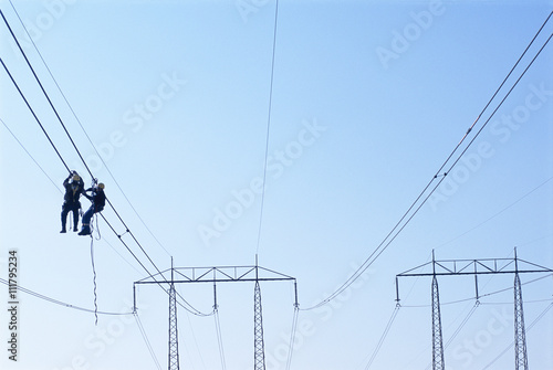 Men working on power lines, low angle view