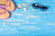 View of sunglasses seashells and flip-flops lying on blue wooden background. Travel concept.