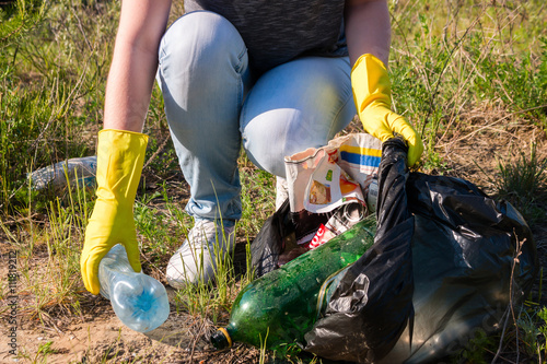 Fotografie, Obraz  Volunteer girl in yellow gloves collects garbage selective focus