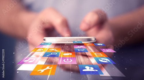 Photo Man holding smart phone with colorful application icons
