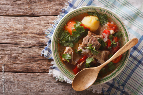 Photo Stands Ready meals Shurpa lamb soup with vegetables closeup at the plate. horizontal top view