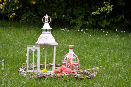 Photo  lantern on grass in vintage style, decorated bottle of alcohol with symbolic signs and patterns