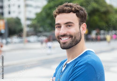 Fotografie, Obraz  Lachender Mann mit Bart im blauen Shirt in der Stadt