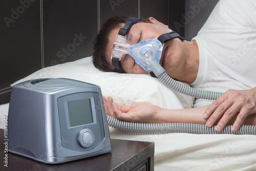 Photo Asian man with sleep apnea using CPAP machine