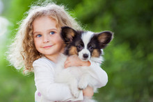 Little Curly Girl With A Papillon Puppy, Outdoor Summer
