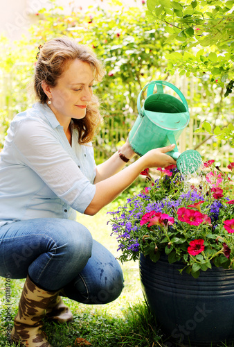 Staande foto Tuin Portrait of beautiful 40 years old woman gardening on sunny day
