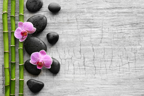 Photo  Spa stones, bamboo and orchids on wooden background
