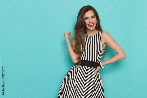 33184eb39f9 Smiling girl in black and white striped dress posing with fist raised and  looking at camera