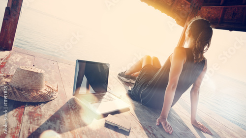 Deurstickers Ontspanning Woman relaxing and listening music at sunrise. Blurry effect, lens flares effect, intentional sun glare