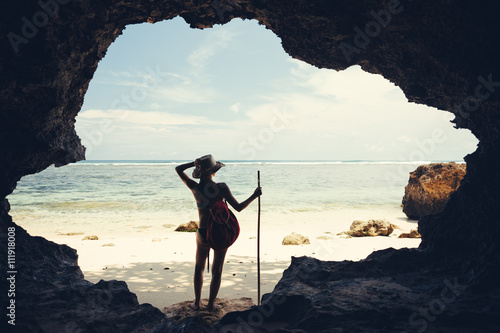 Fotografia  Silhouette of young woman standing in cave on the beach with hat, stick and back