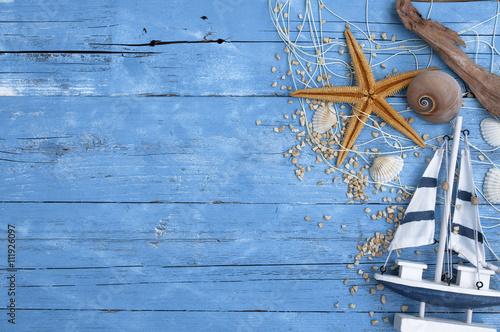 Maritime Dekoration auf blauem Holzhintergrund mit Holzschiff, Seestern, Muscheln, Treibholz ud Fischernetz
