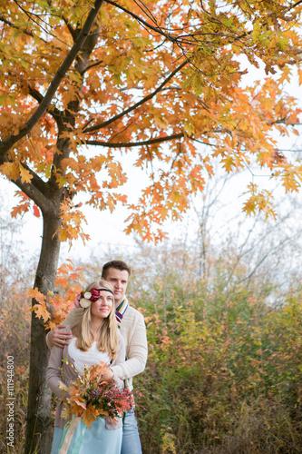 Fototapeta Autumn wedding in boho style. Autumn leaf fall, autumnal forest. loving couple, man and woman. orange pumpkin obraz na płótnie