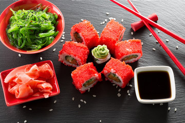Fototapetasushi and rolls with green sea salad on a slate table