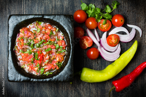 Tomato sauce salsa and ingredients dark stone background. Fototapet