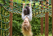 Portrait Of Happy Little Blond Girl Playing On A Rope Web Playground Outdoor