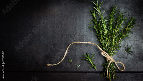 Bunch of rosemary on black background. Top view Fototapet