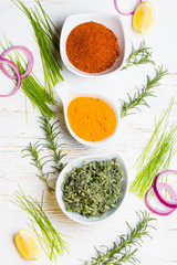 Fototapeta Dry colorful spices in bowls with fresh seasoning on white