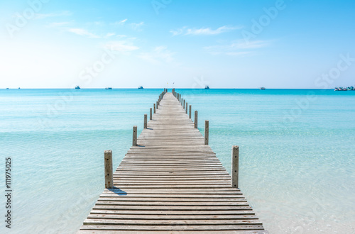 Poster de jardin Ponts Wooden bridge on the beach to the sea in blue summer sky. Jetty
