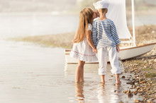 Boy With Girl Walking Along The Shore Of The Lake