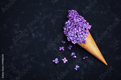 Photo  Ice cream of lilac flowers in waffle cone on black background from above, beauti