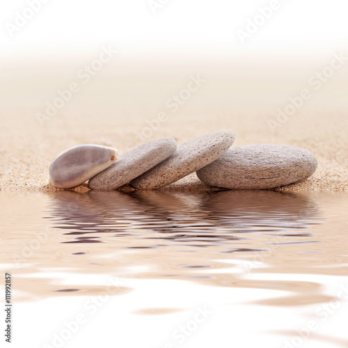 Zen stone stack and sand, water reflections