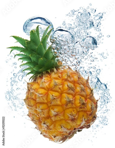 Staande foto Opspattend water Bubbles forming in blue water after pineapple is dropped into it.
