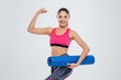 Fitness woman holding yoga mat and showing her biceps
