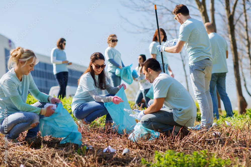 Fototapety, obrazy: volunteers with garbage bags cleaning park area